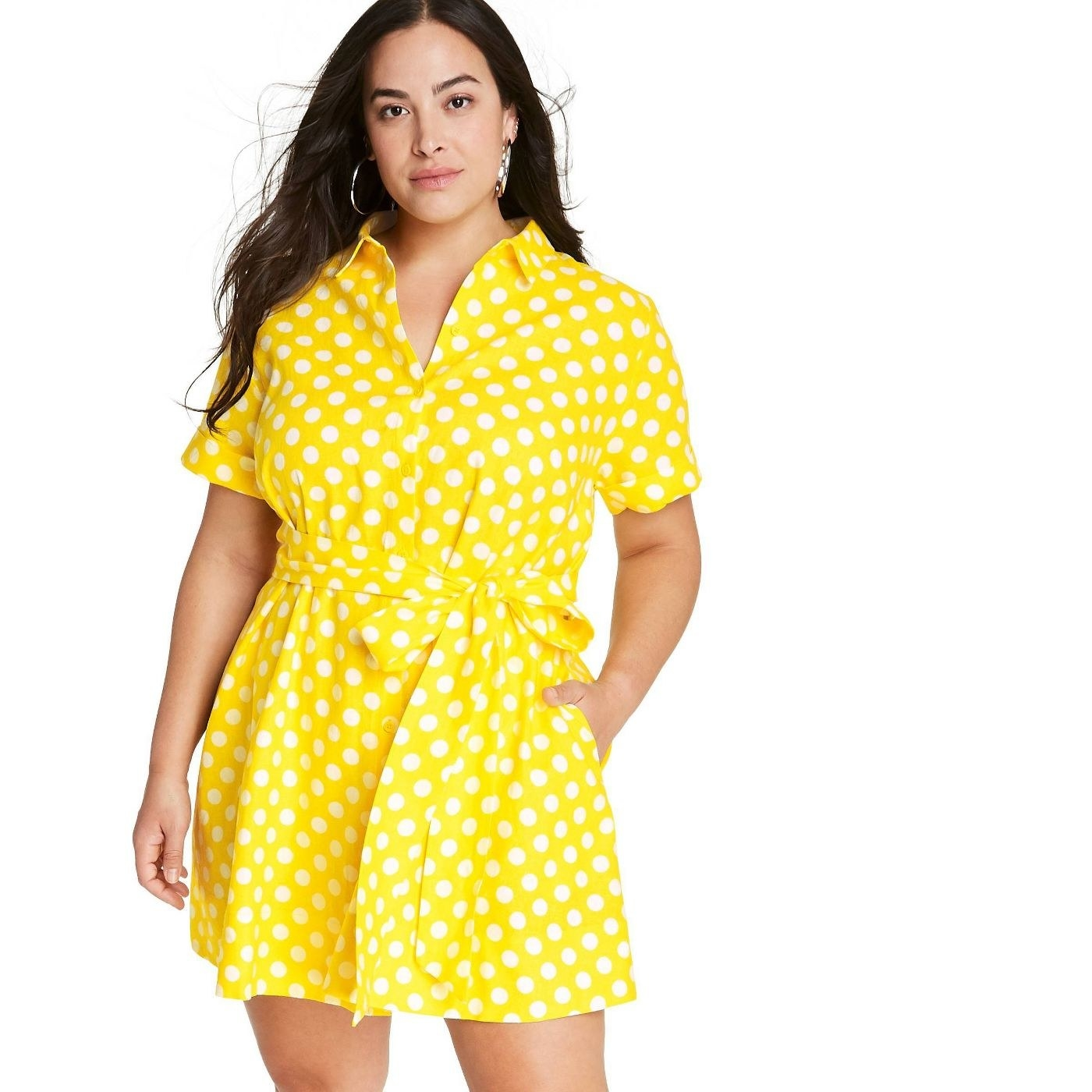 A model in a yellow dress with white polka dots and a tie string waist