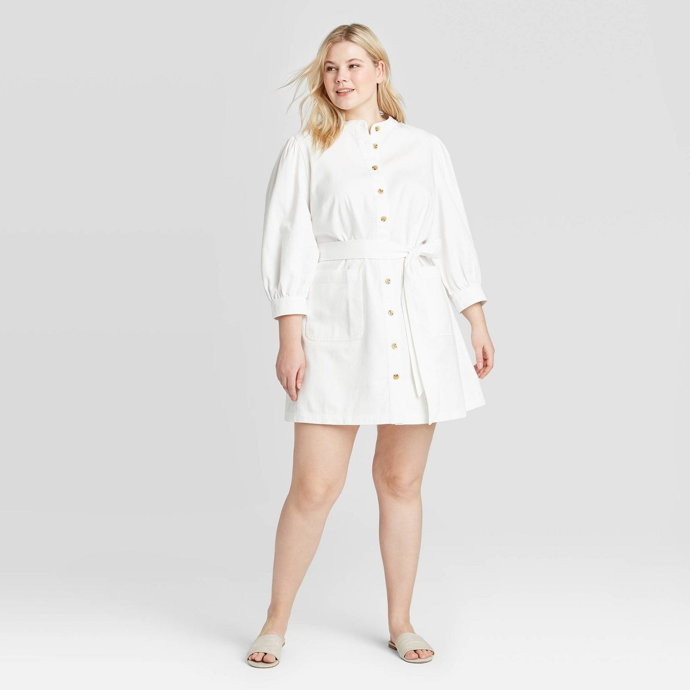 A white long sleeved button up dress that cinches at the waist