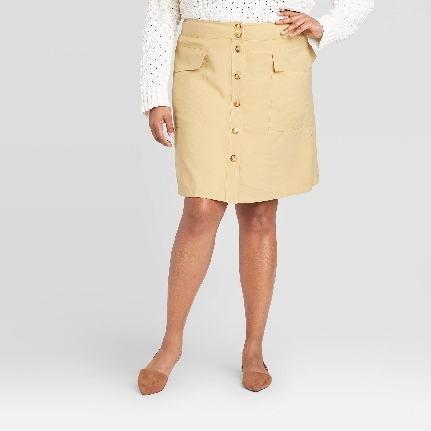 A model in a beige button up skirt that falls just above the knee
