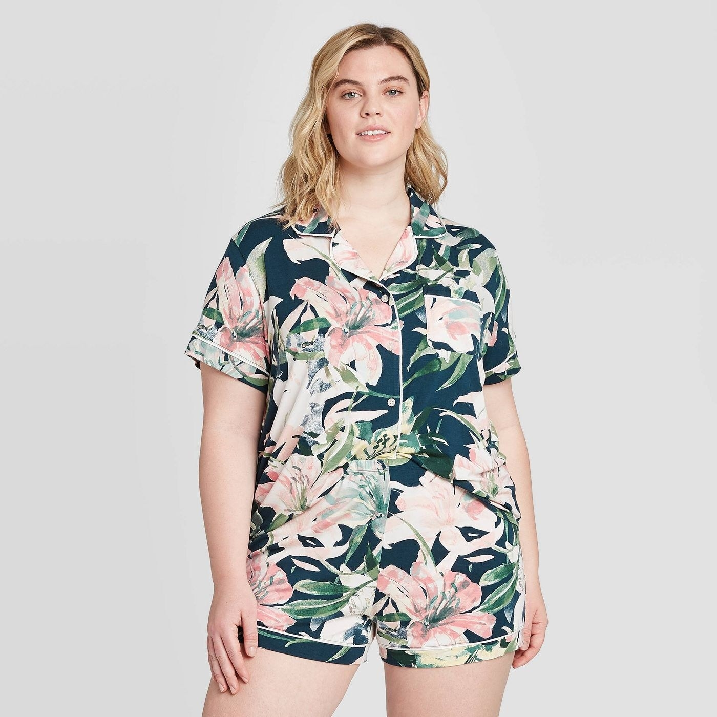 A model in a short sleeve tee and matching pajama short in dark green with pink floral watercolor patterns