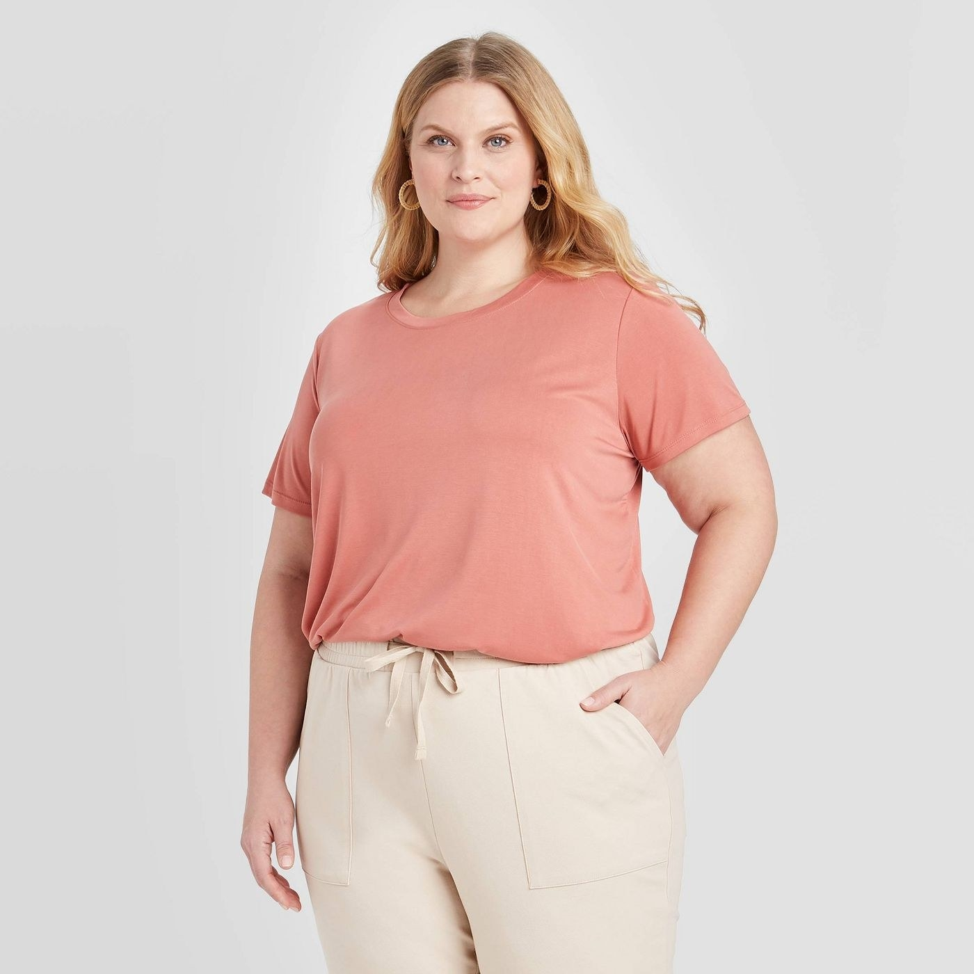 A model in a pink scoop neck tee
