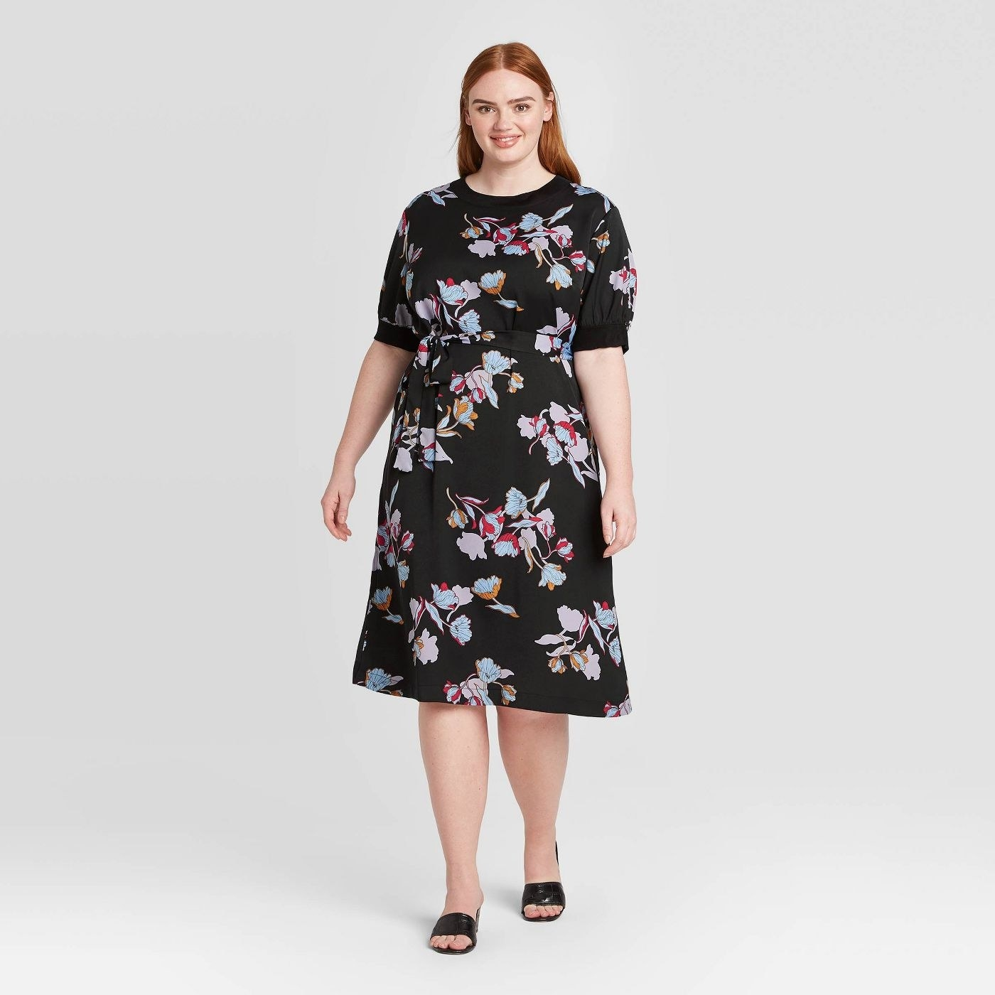 A model in a black short-sleeved dress with purple florals