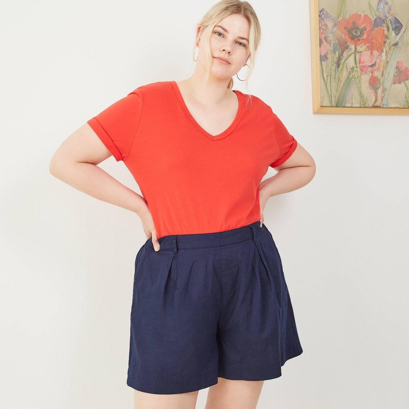 A model in high-waisted navy blue shorts