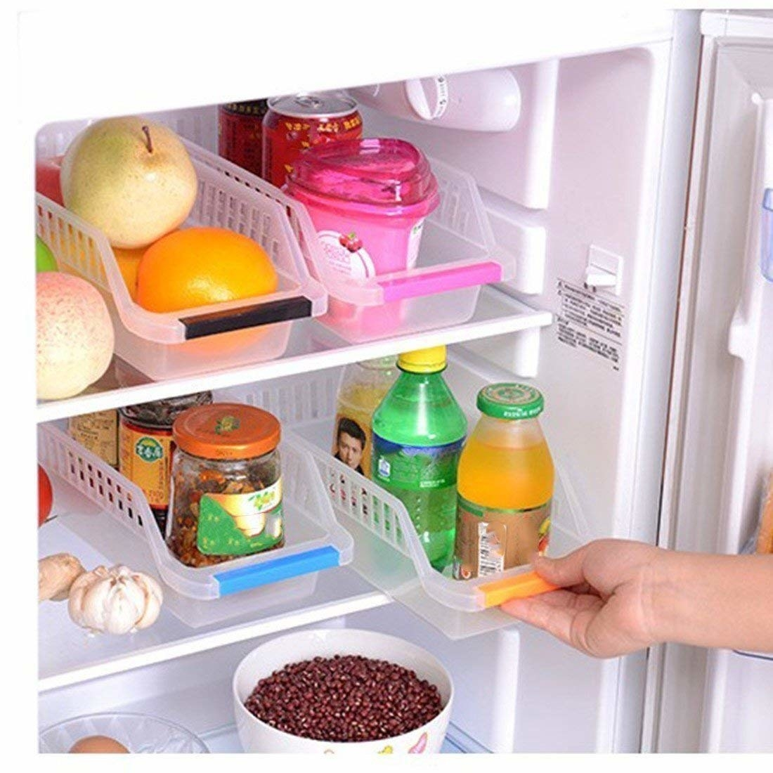 A hand pulling out a fridge organiser. They are used to hold fruits, jars, juice bottles.