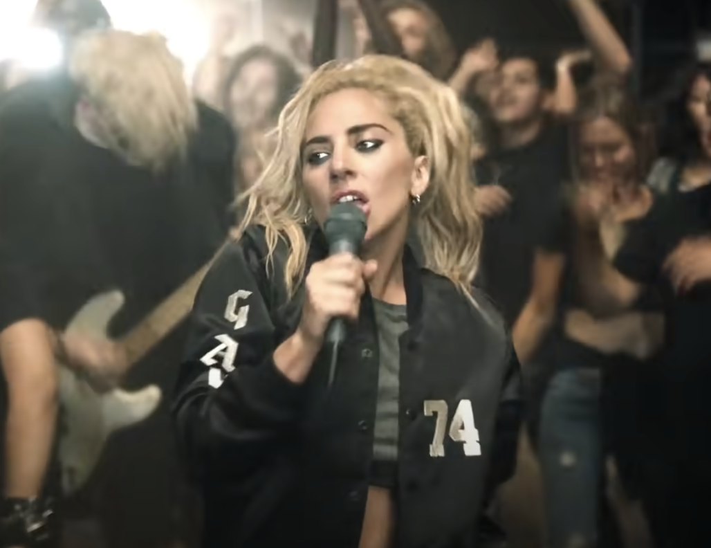 Lady Gaga sings into a microphone while wearing a varsity jacket