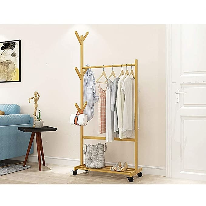 The clothes rack used to store shirts, dresses, shoes, a handbag and a laundry basket.