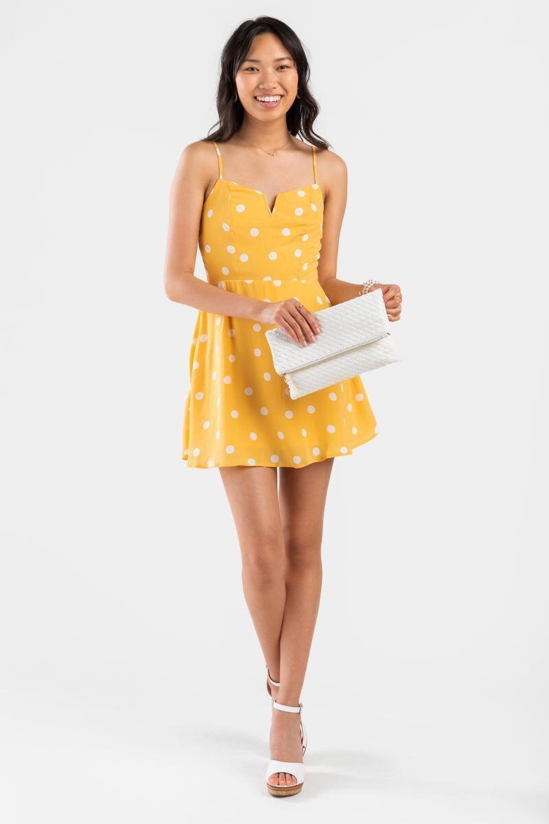 A model wearing a yellow polka dot spaghetti strap mini dress