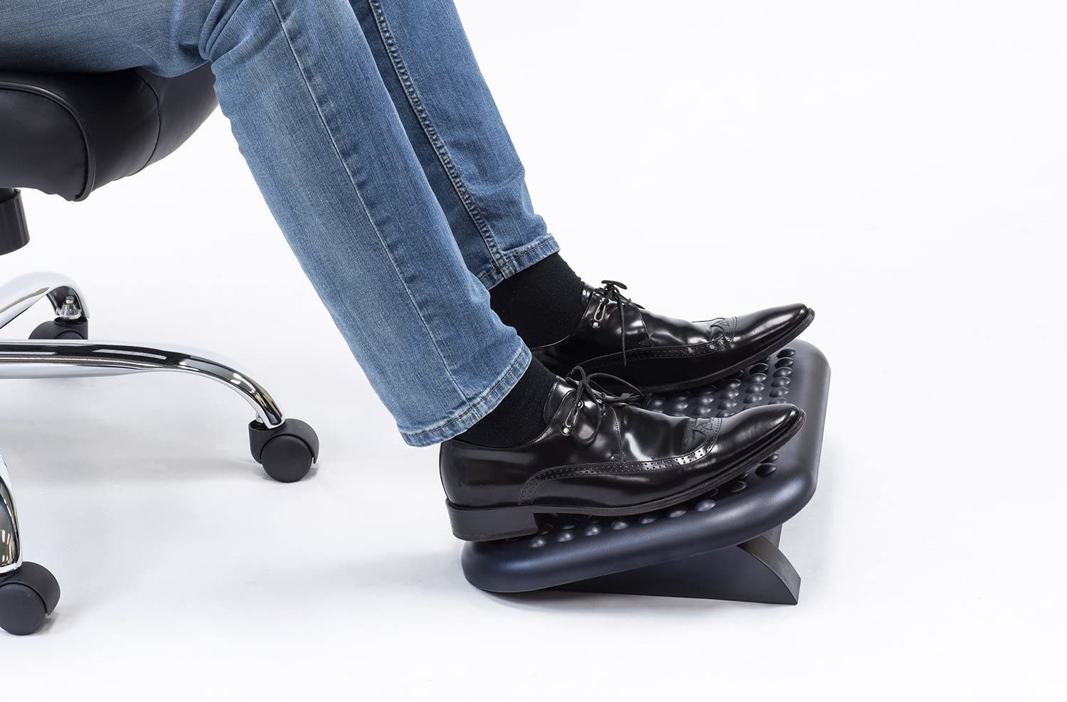 A person rest their feet on an angled foot rest with a bumpy surface