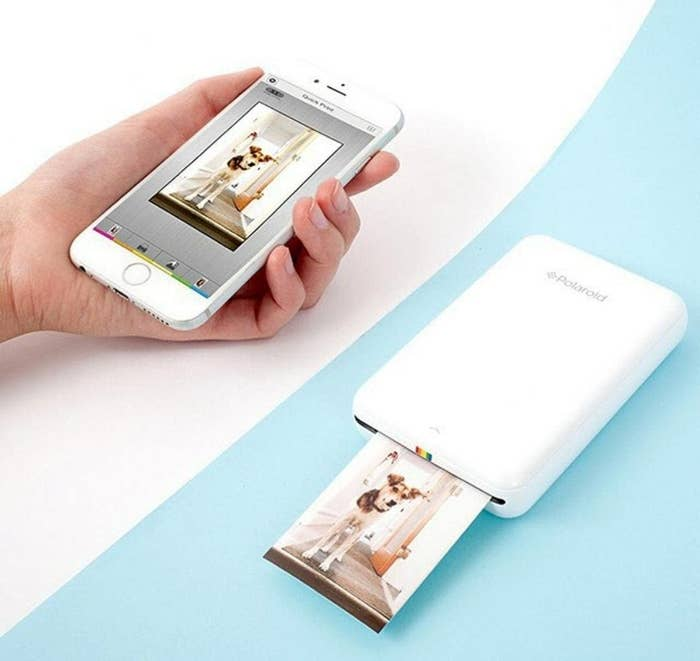 A white mini printer about the size of a phone printing an image from a phone
