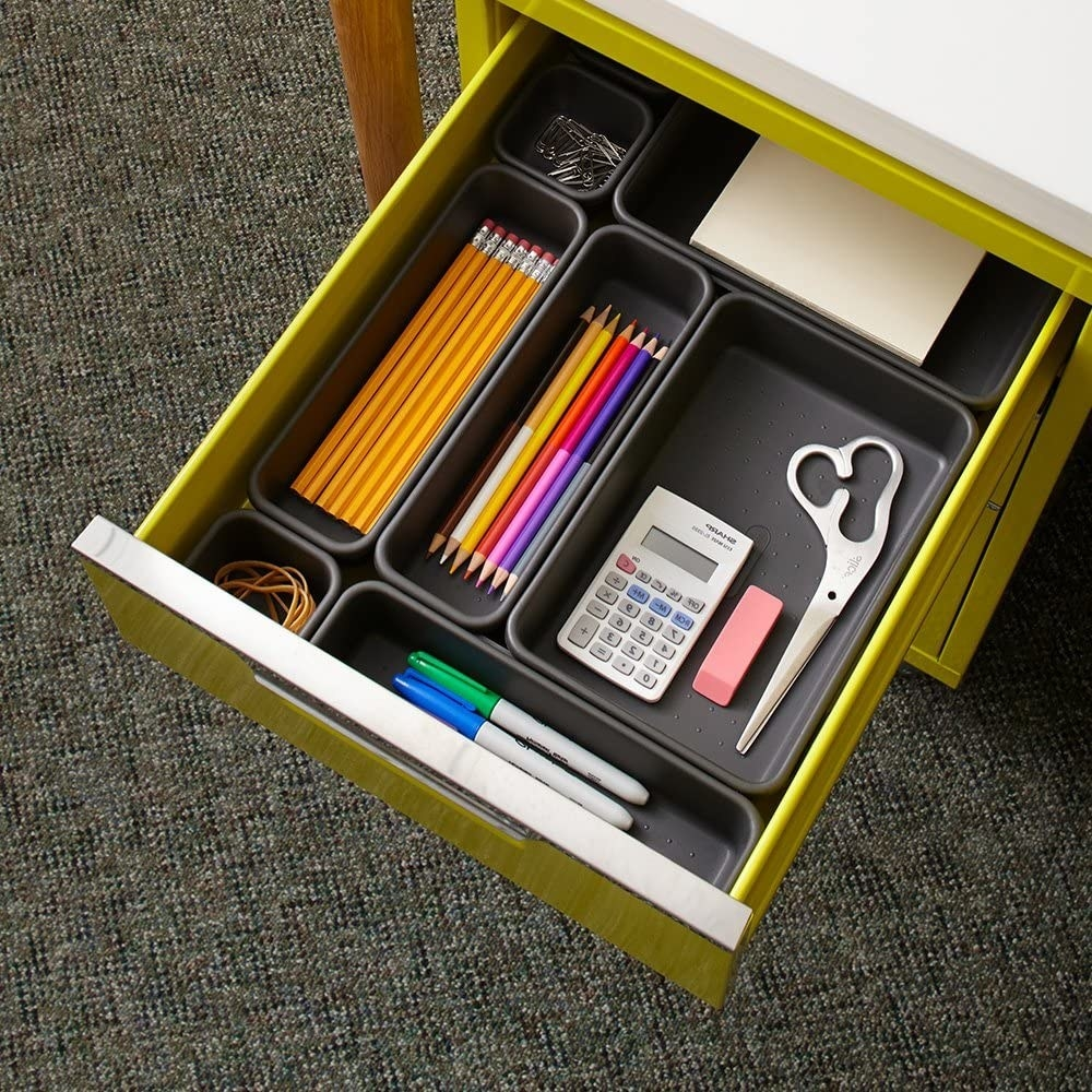 A open desk drawer with containers of different sizes Office supplies like pencils, scissors, and elastic bands are organized in each bin