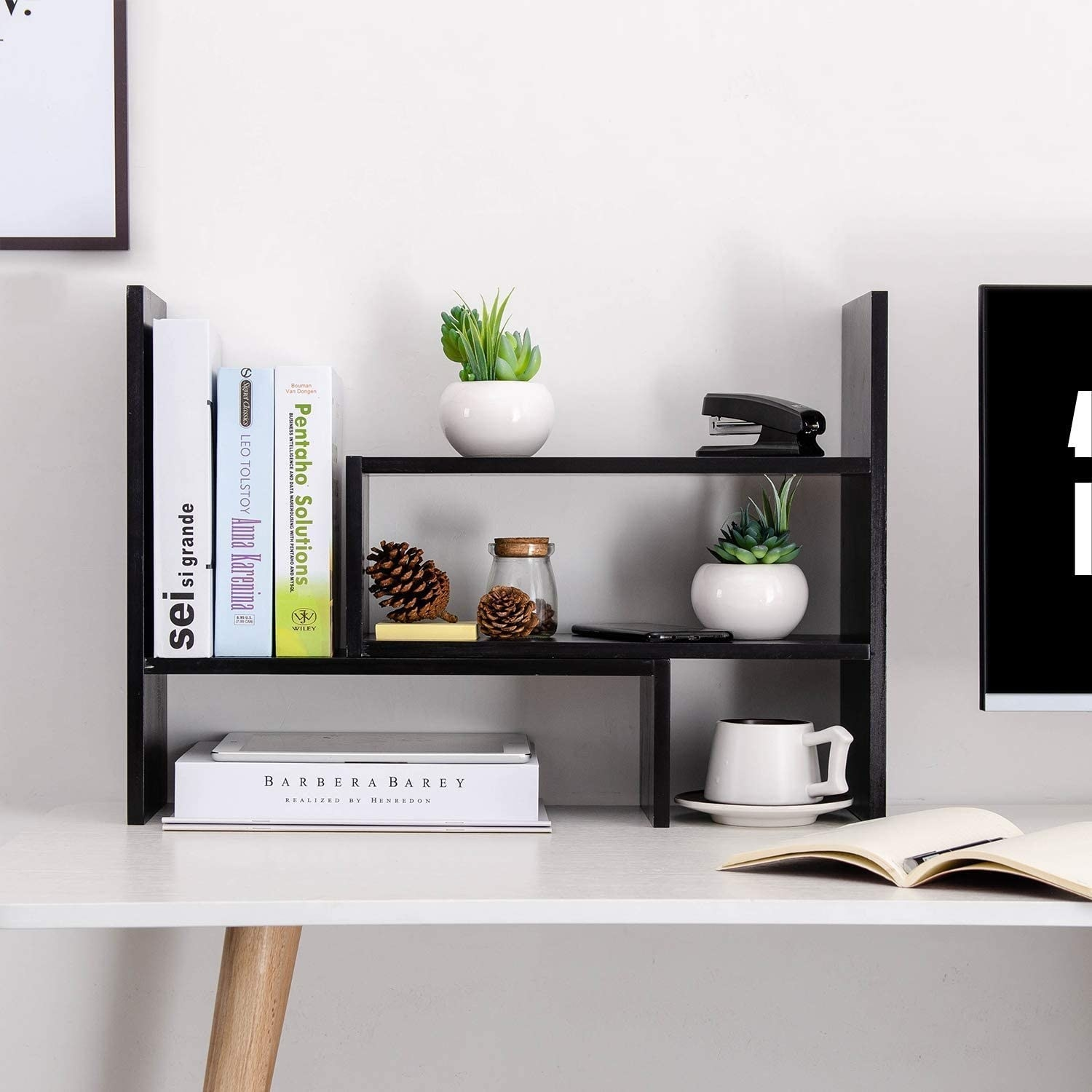 A small adjustable desk organizer with multiple shelves in a tiled pattern A set of books, plants, and other desk knickknacks sit on the shelves