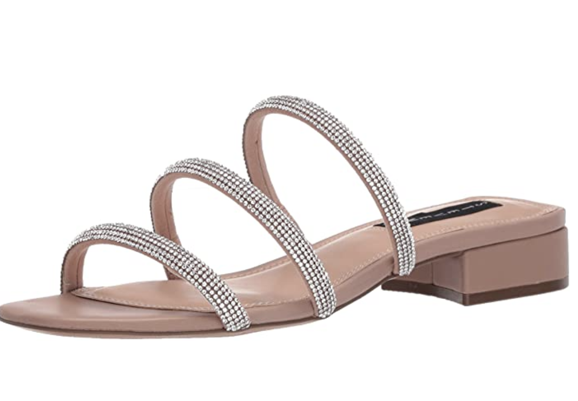 A beige open-toed sandal with a low heel and three straps with metallic detailing