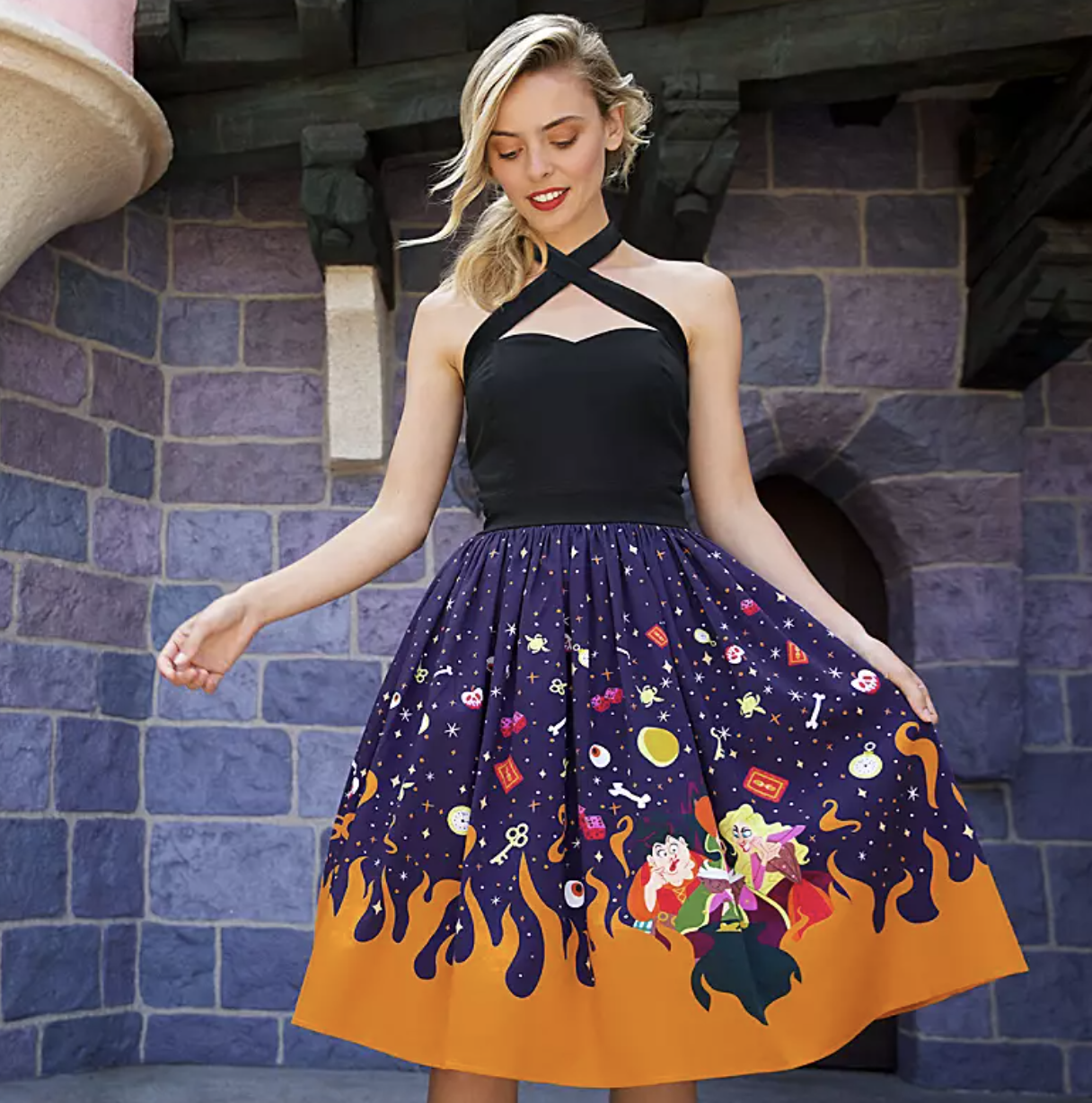 a halter dress that criss-crosses in the front, cuts into a black sweetheart neckline, and has a flowing skirt with a purple base, orange flames licking up from the bottom, and an array of hocus pocus themed icons all over