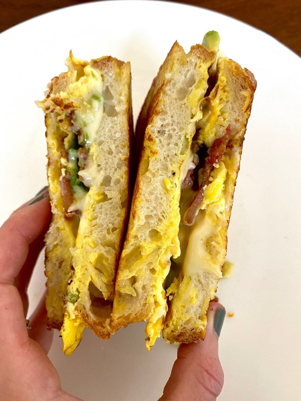 Hands holding a cheesy bacon, egg, and cheese sandwich sliced in half.