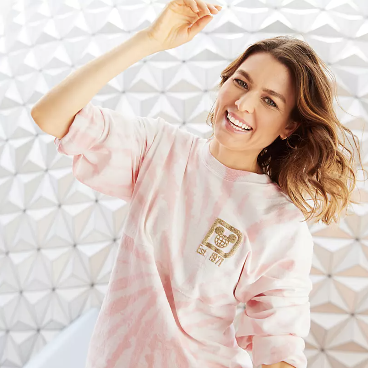 a model wearing a white and light pink tie dyed long sleeve with the Disney World logo in gold glitter