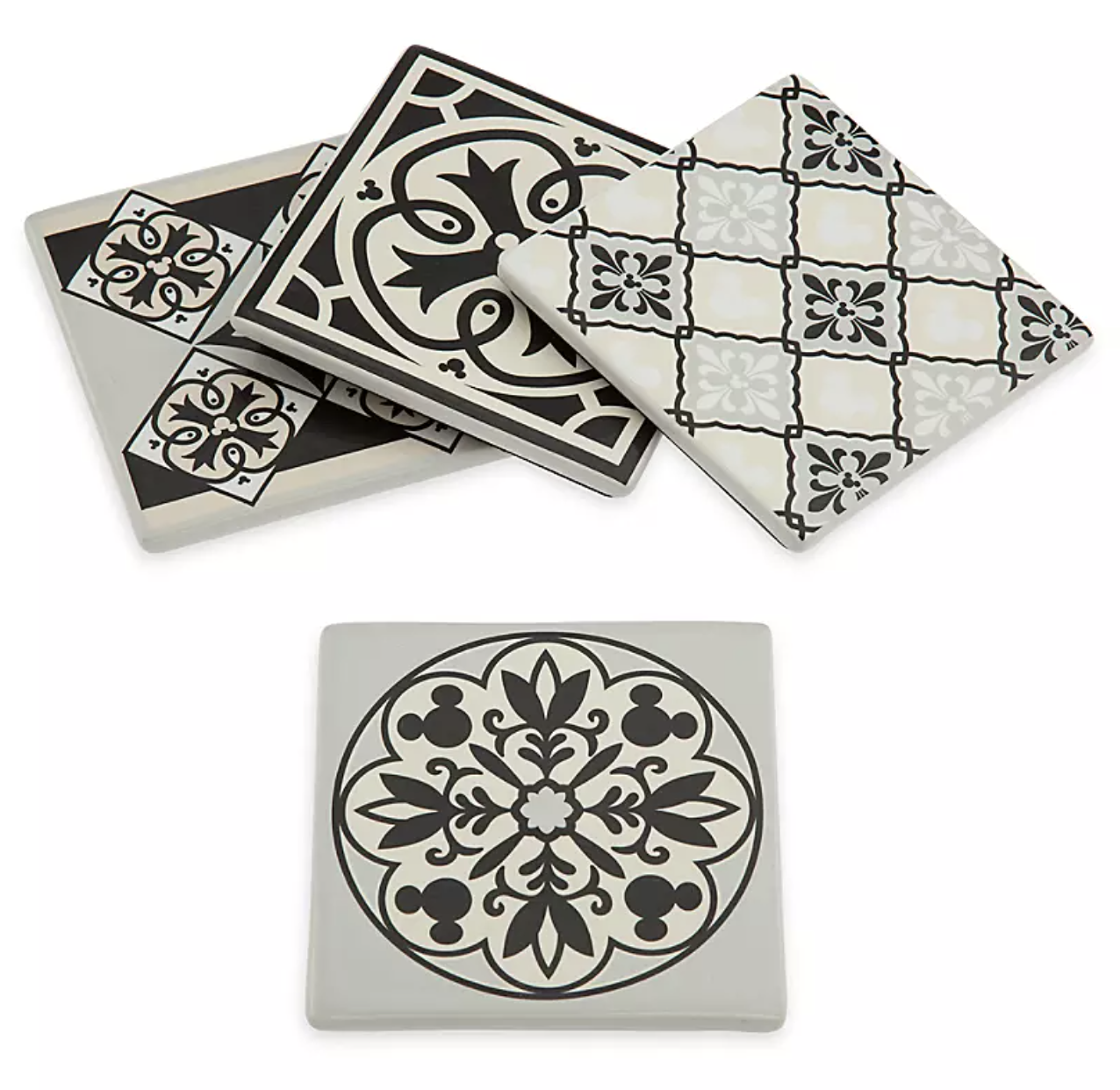 four different white coasters with intricate black designs on them, each including mickey somehow