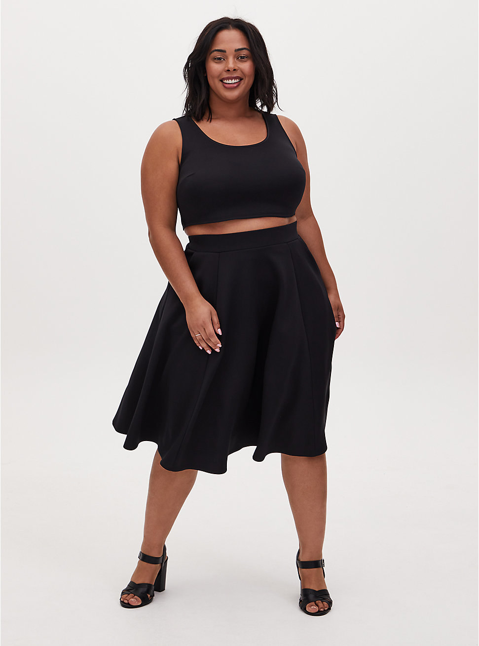 model in tight black tank crop top and black high-waisted midi skirt