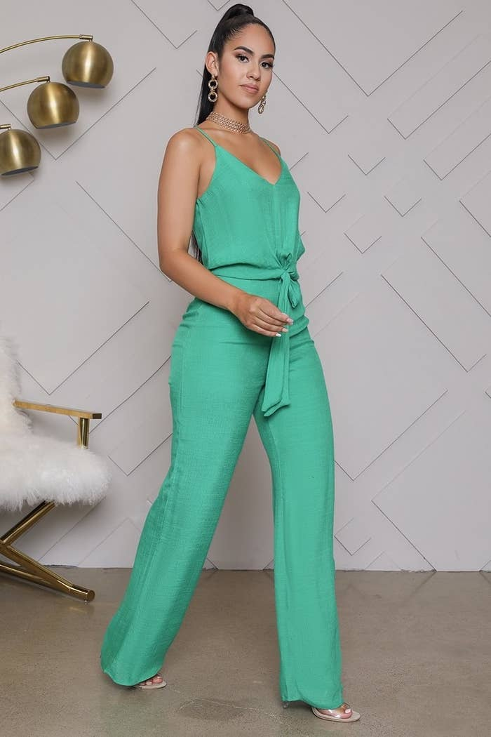 model in kelly green jumpsuit with waist tie