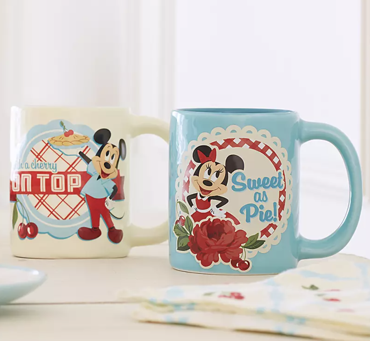 "an off white mug with a retro design of mickey on it that says ""with a cherry on top"" and a light blue mug with a retro design of minnie on it that says ""Sweet as pie!"" on it"