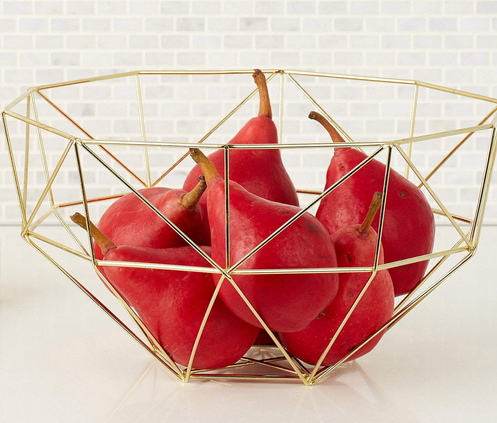 A metal bowl with pears inside it