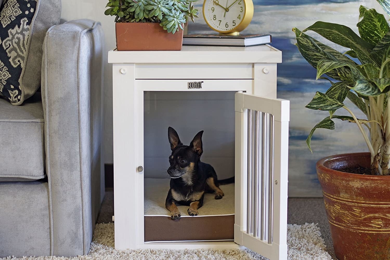 A lifestyle shot of a chiwawa laying inside of the side table crate with the door open. The table is beside a sofa and has a plant, clock, and book as decor on top.