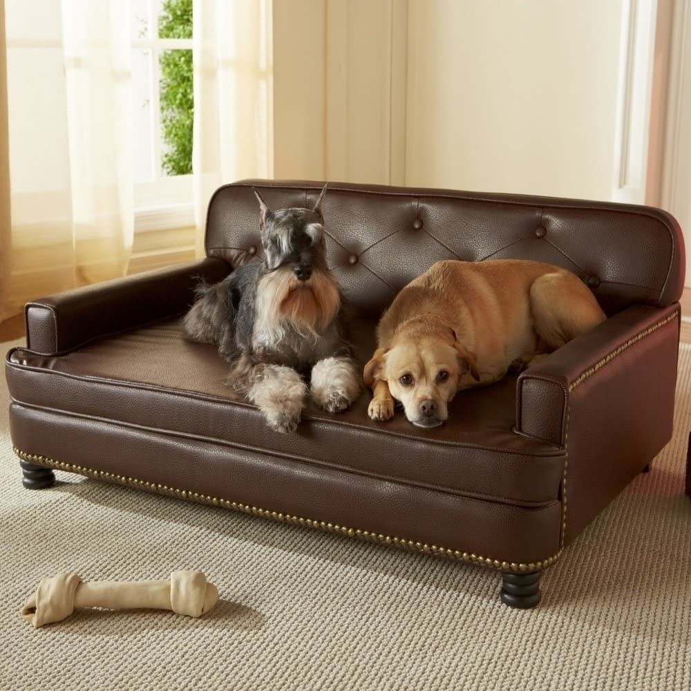 A product shot of the tufted leather sofa with two medium-sized dogs sitting on it