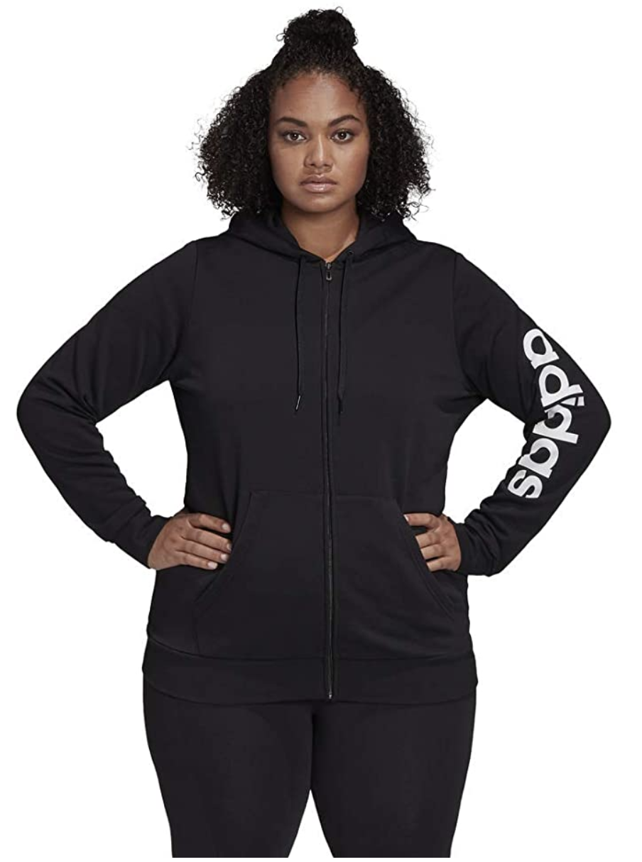 "A model in a black drawstring hoodie with front pockets and the word ""adidas"" written in white on the left arm"