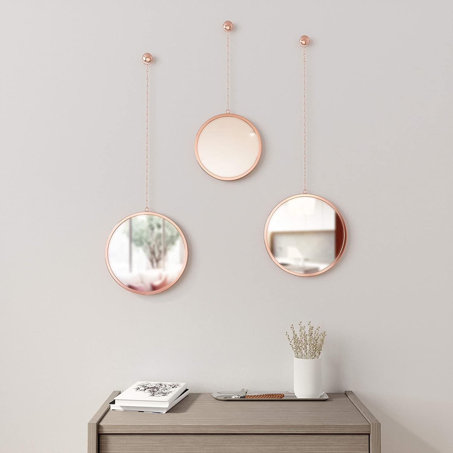 Three round framed mirrors hanging on a wall