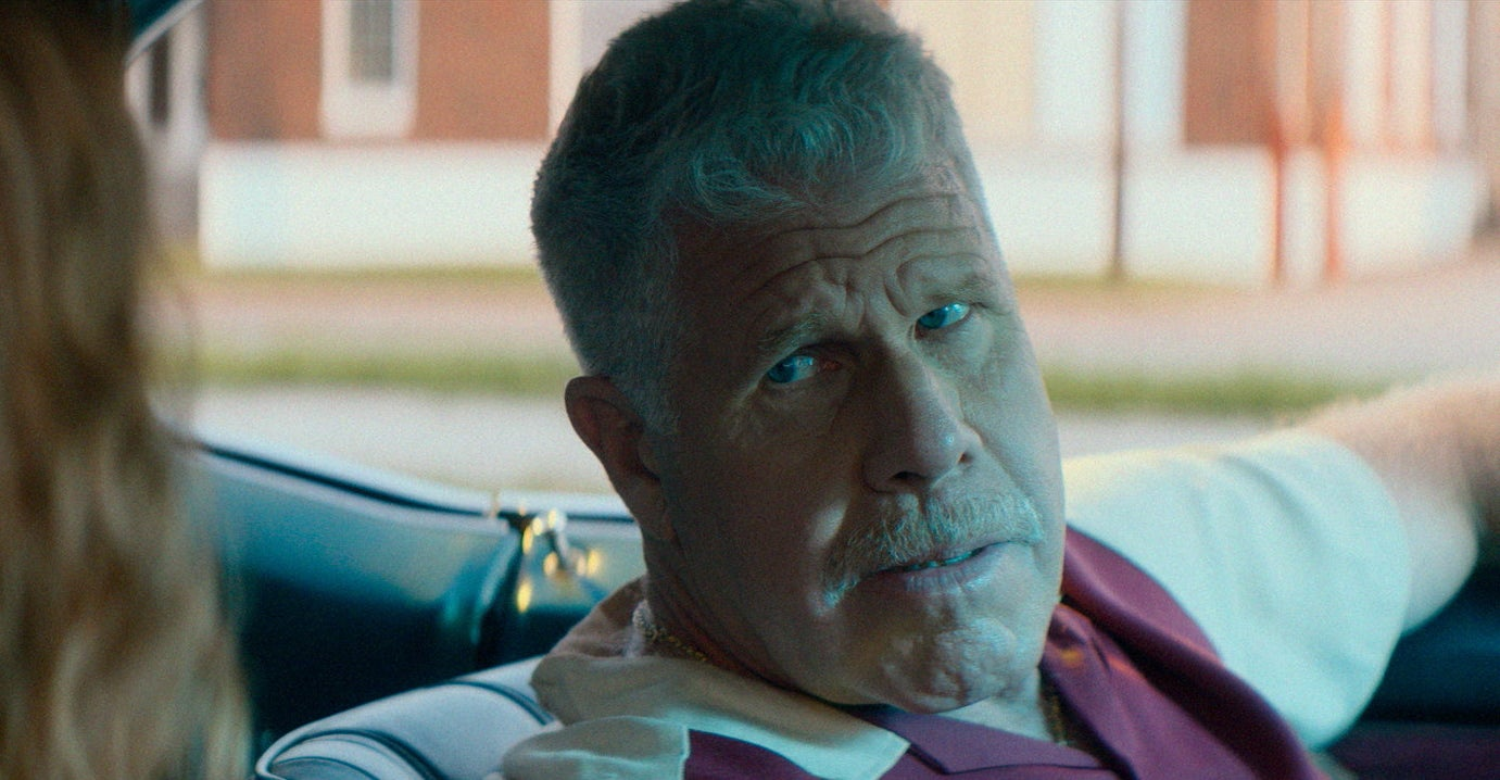 Ron Perlman in a car looking at a woman.