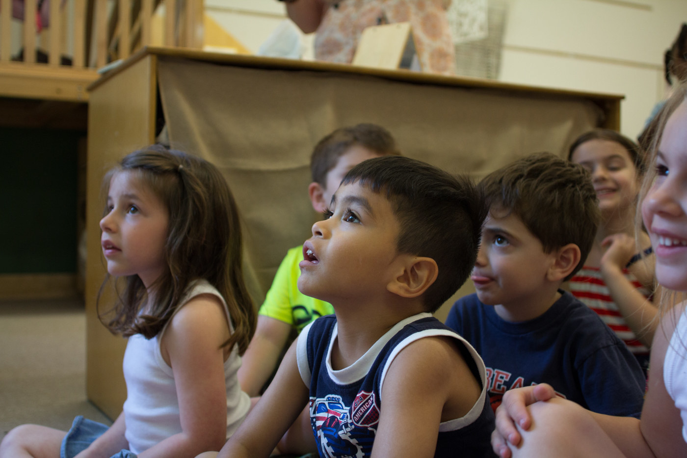 A group of children sitting on the floor and watching something.