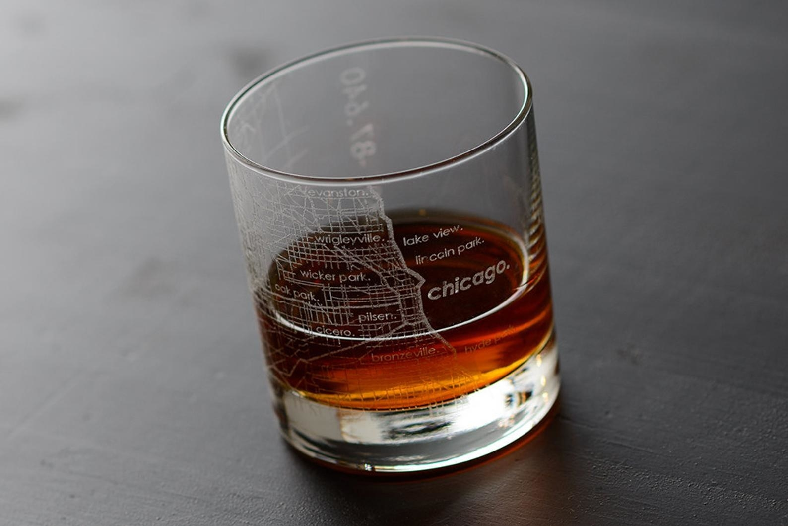 A whiskey tumbler with the map of Chicago etched on it