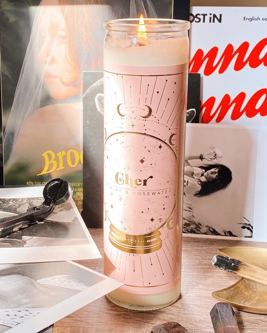 "Votive candle with pink label and gold illustration of a crystal ball with the words ""Cher"" and ""Jasmine & Rosewater"" in it"