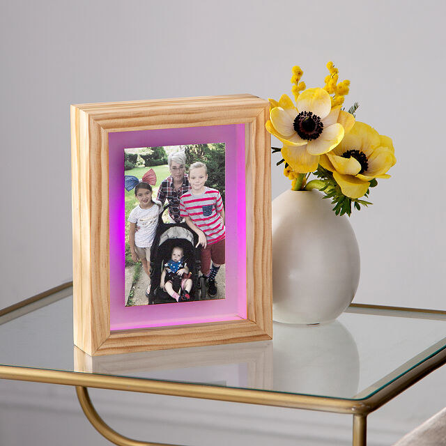 A picture frame with a pink light at its edges