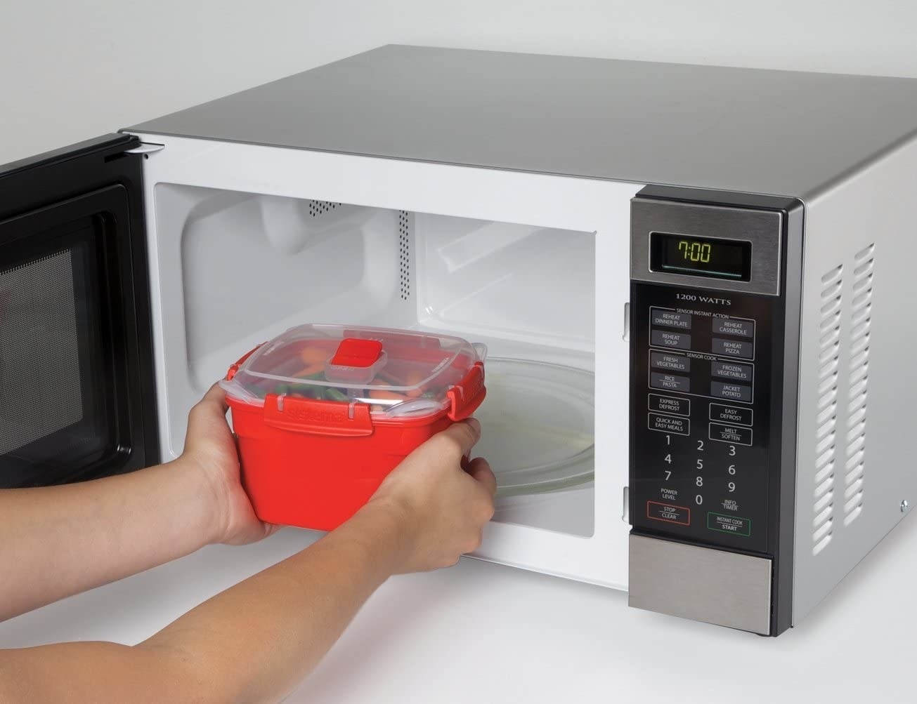 Hands putting the red steaming container and lid in a microwave