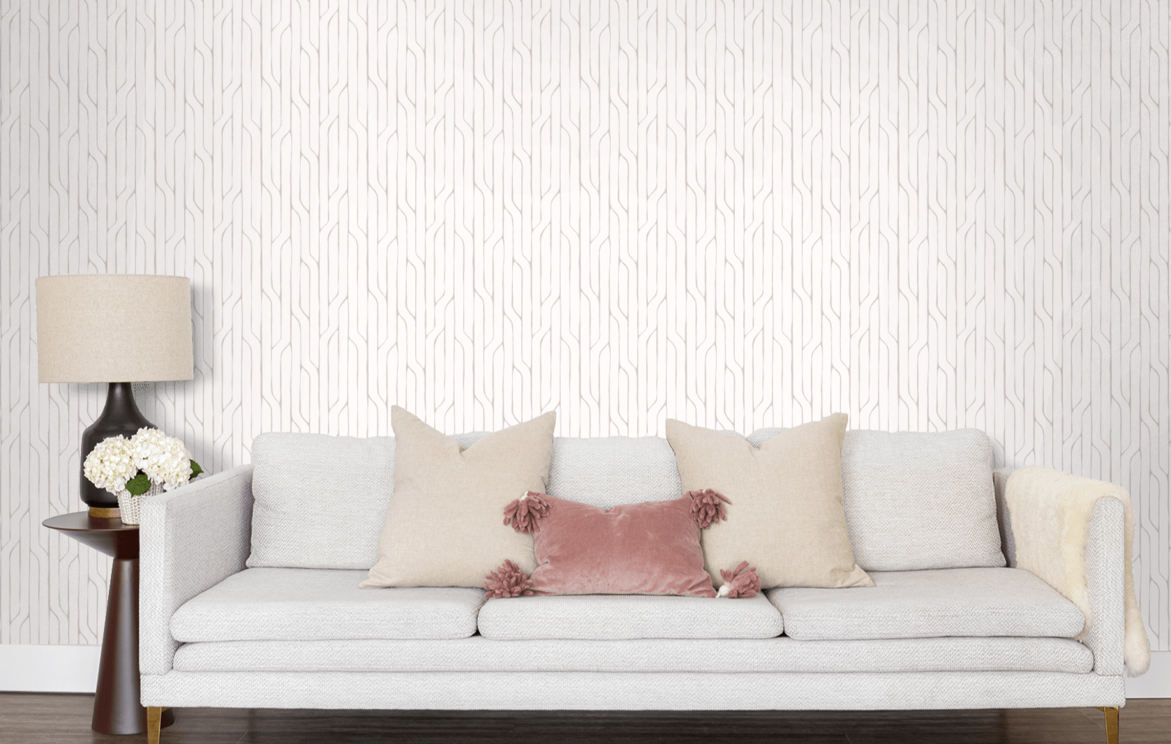 A sofa in front of a wall with the white and grey geometric wallpaper on it