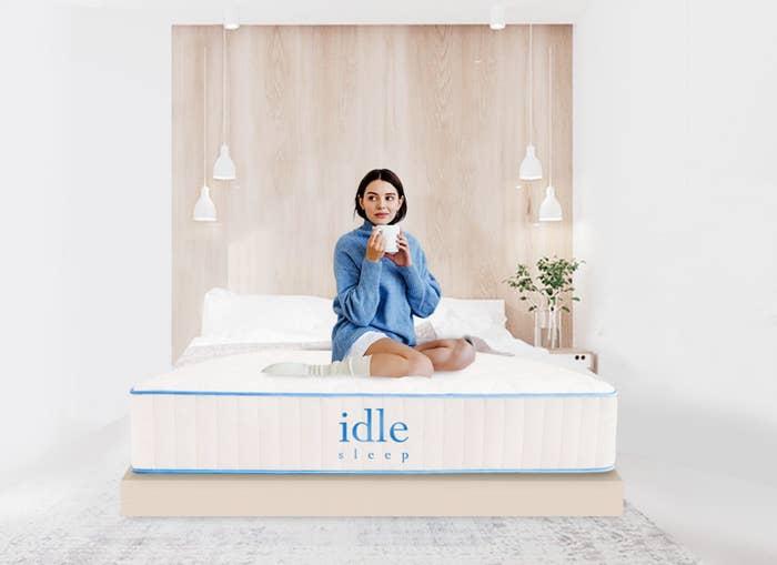 Model in blue sweater drinking coffee on mattress