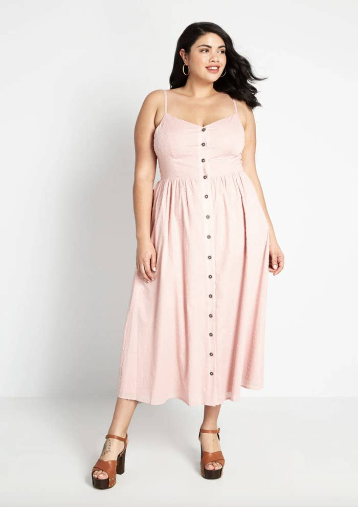 A model in a pale pink dress with straps