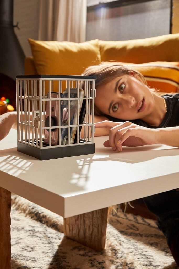 A model looking at their electronic devices inside the cage-inspired lock box