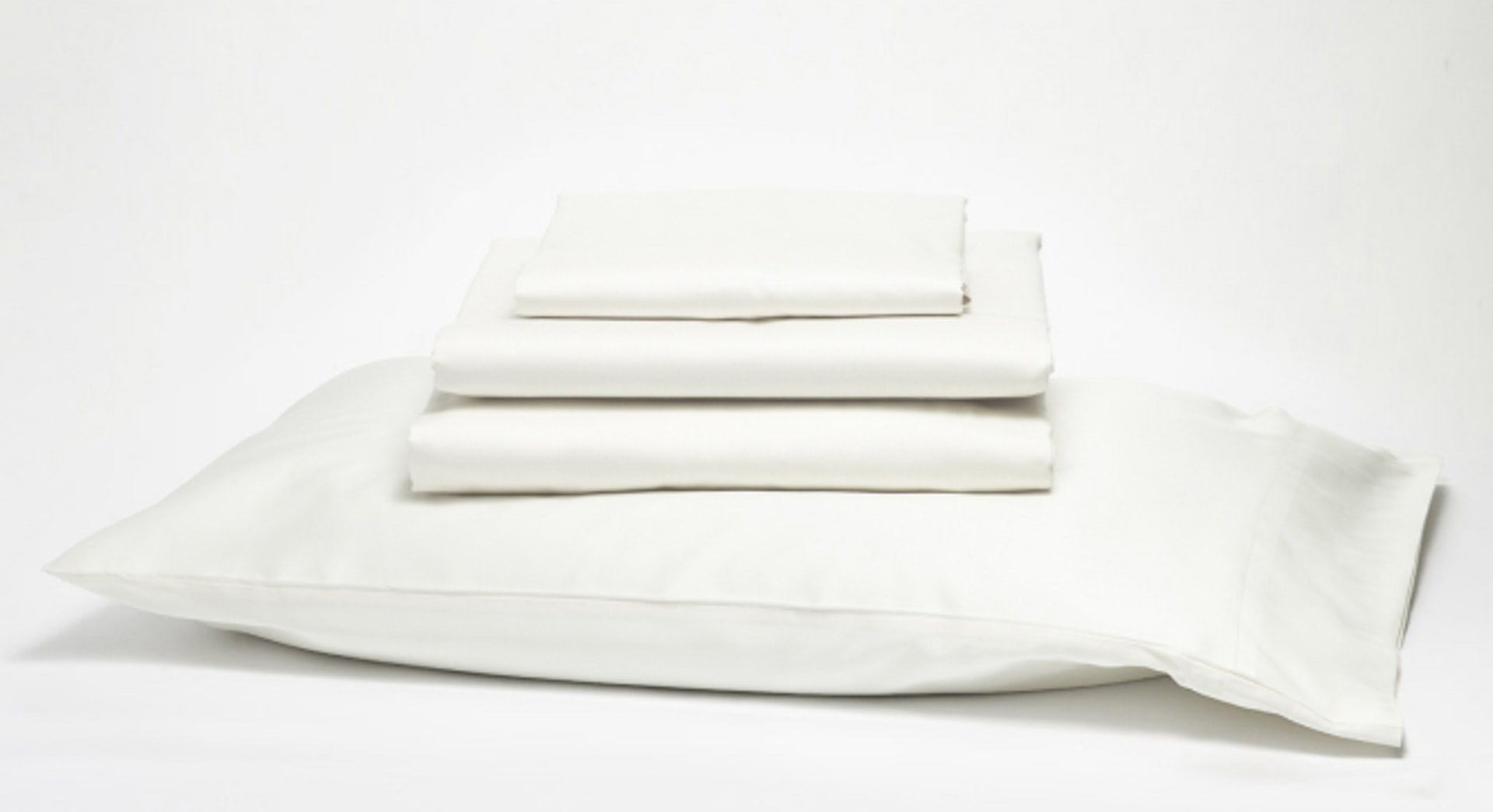 Pillow with white sheets stacked on top