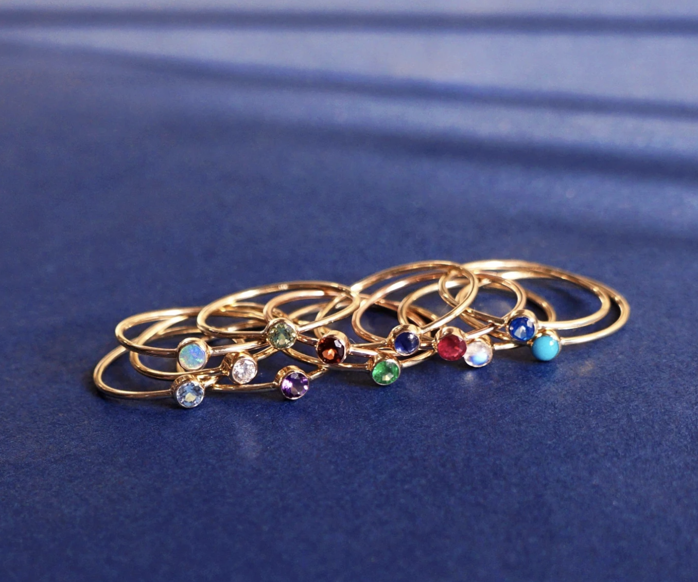 The 12 different birthstone rings arranged on a surface