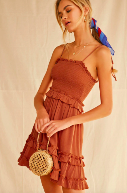 Model wears a rust-colored sleeveless tiered dress with ruffles