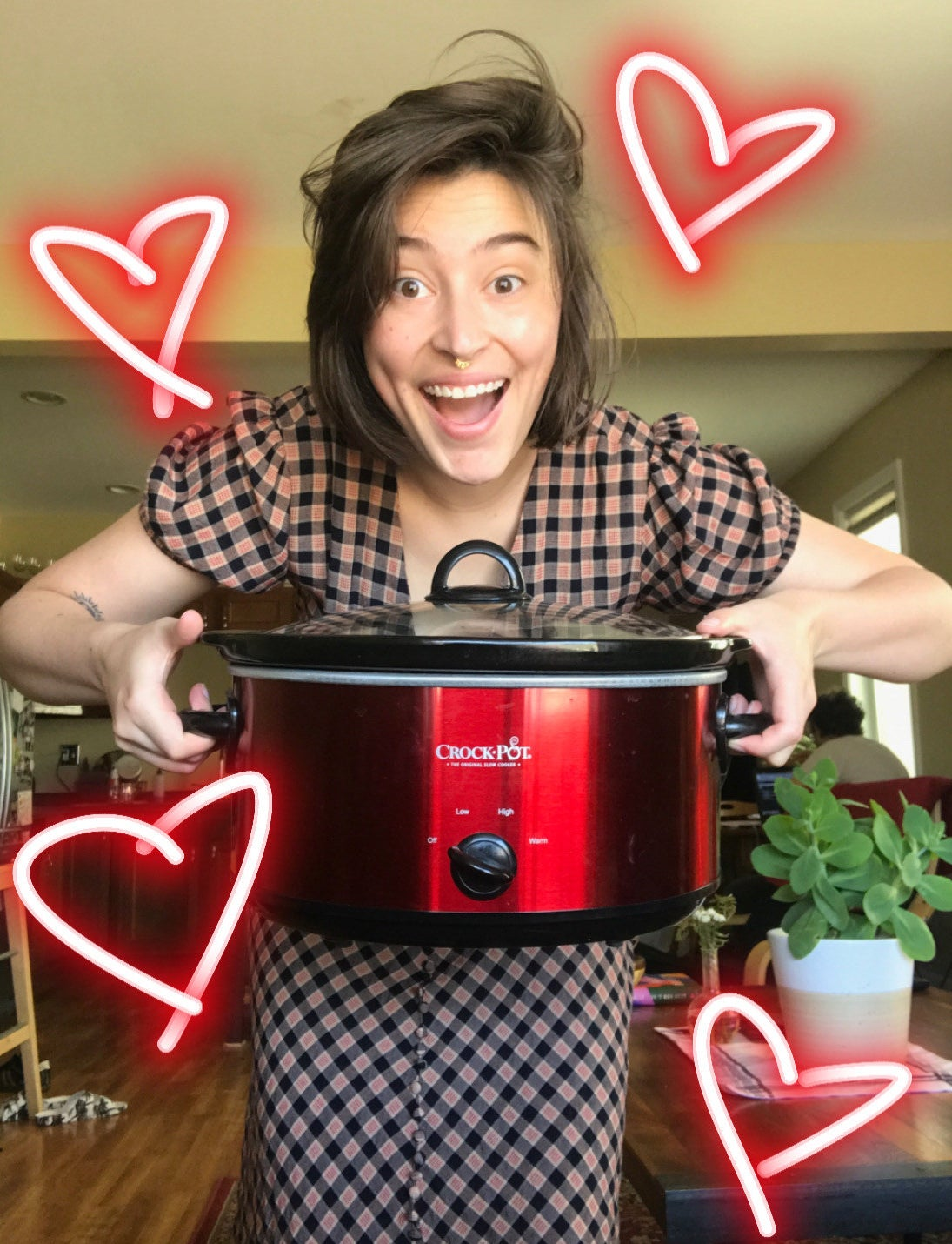 writer holding red crock-pot with hearts drawn around it