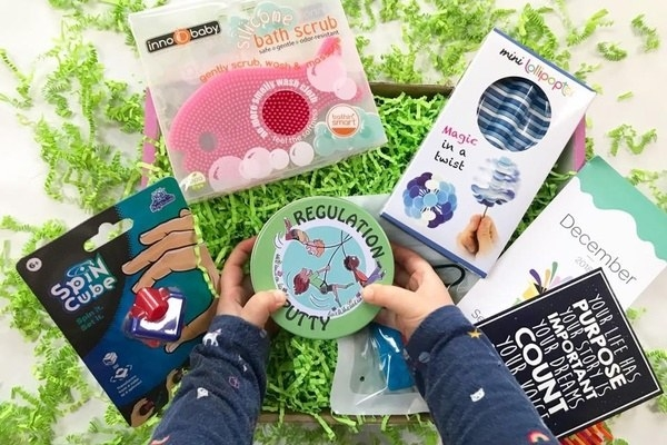 Featured sensory items and child's hands reaching for regulation putty