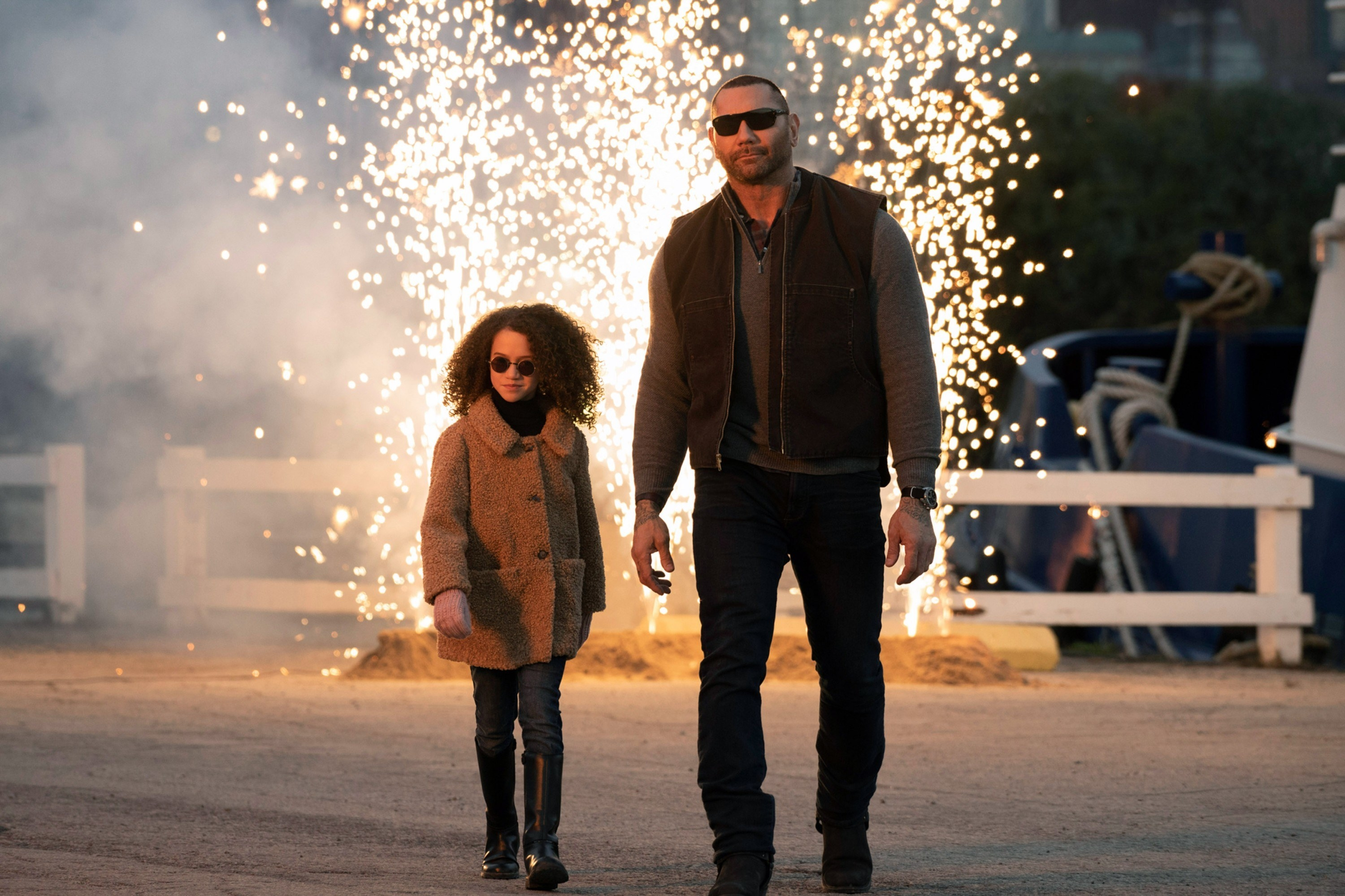A girl and Dave Bautista walk away from an explosion with sunglasses on.