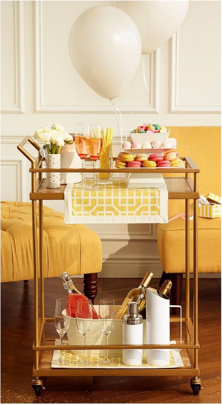 a brass bar cart with a lower shelf and a top shelf in addition to wheels