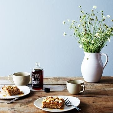 breakfast table setup with coffee cake on plates and spicy syrup bottle