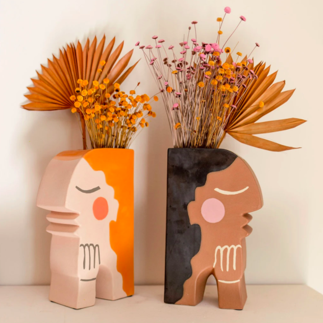 two vases shaped like faces with flat backs and holes on top for flowers