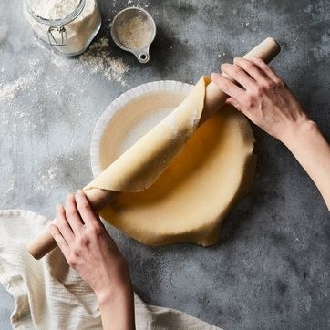 hands using the rolling pin to roll pie crust onto a pan