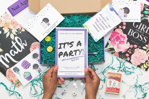Hands displaying a Black Girl Mathgic workbook with stickers, historical playing cards, and other featured items scattered around
