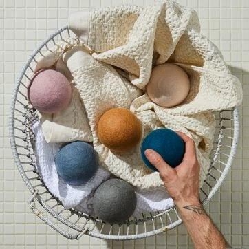 hand reaching into laundry basket with towels to reach a tennis ball sized wool ball